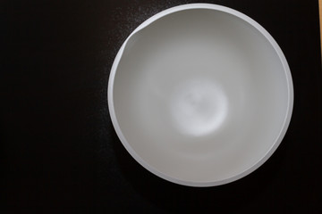 A bowl for kneading the dough with a white bottom is on the table