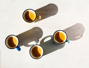 Cups of coffee. Four cups of Espresso on a table back lit by the sun casting a long shadows
