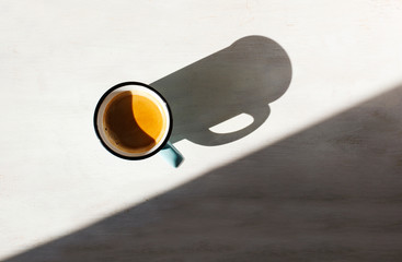 Cup of coffee. Сup of Espresso on a table back lit by the sun casting a long shadow