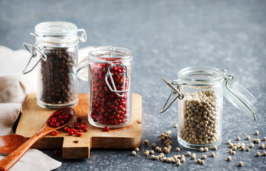 Pink, White and black peppers in a glass jars