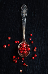 Pink peppers in spoon, top view
