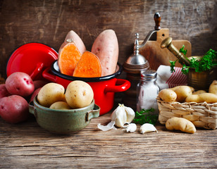 Variety of raw uncooked organic potatoes: red, white, sweet  and fingers potatoes over wooden background.