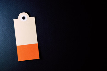 vertical decorated rectangle paper tag on dark background