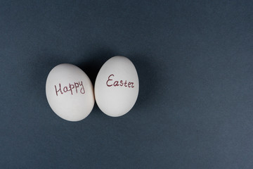 Happy Easter text on white eggs isolaed on grey background. Easter holiday concept. Flat lay. Top view.