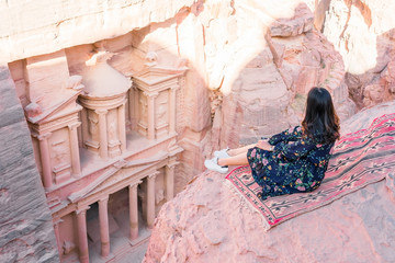 Aerial view of the Treasury with a hiker, solo traveler, young woman tourist sitting on a cliff after reaching the top, Al Khazneh in the ancient city of Petra, Jordan, UNESCO World Heritage Site