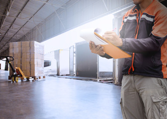 Logistic and warehouse. warehouse worker is writing on clipboard with checking shipment for load into a truck. Wall mural