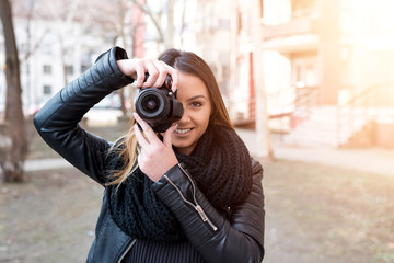 Young woman taking pictures outside.