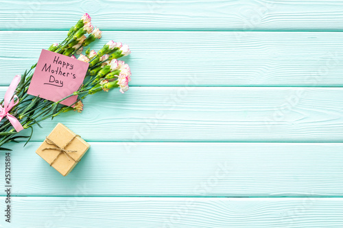 Happy Mother's Day concept. Hand lettering near bouquet of pink carnation and gift box on blue turquoise wooden background top view space for text