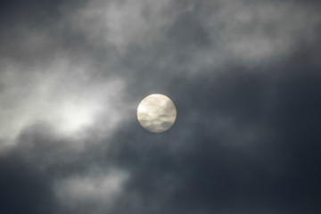 The sun is covered with dark clouds, the sun defocused in the clouds.