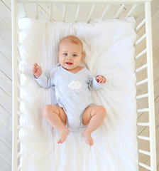 Charming smiling blue-eyed 9 month old baby in a gray bodysuit is lying in a child's bed. Top view