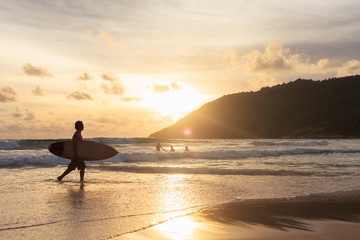 silhouette of man with surfboard on the beach at sunset