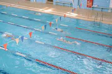 Swim in swiming pool. Closed pool. Swim for speed. Swimming competition.