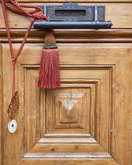 """""""EPISTOLAI"""" letterbox and handle on brown solid wood door closeup with red cord"""