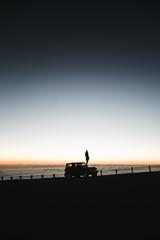 Tourist admiring breathtaking sunset views from the Mauna Kea.