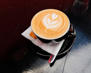 art cappuccino coffee with heart shaped tree in black cup on dark background