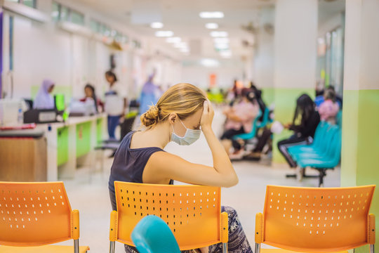 Young woman sitting in hospital waiting for a doctor's appointment. Patients In Doctors Waiting Room