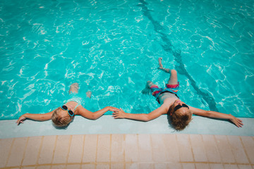little boy and girl relax in pool, family on beach resort