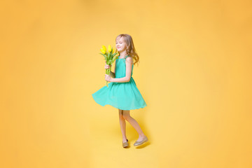 Funny baby girl dancing with a bouquet of yellow tulips. Concept of holidays, fashion and beauty.
