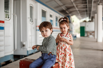 Photo shoot in vintage style. Boy and girl in vintage clothes with vintage accessories on abandoned train station