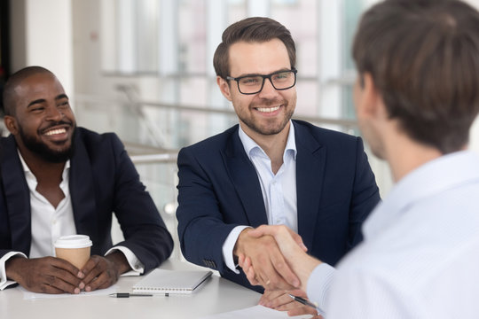 Positive diverse business partners shaking hands starting meeting