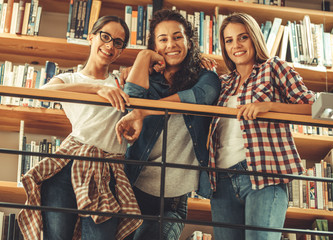 group of female students stands by the book shelf at the campus library.