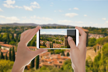 A man is making a photo of tuscan landscape near Florence on a mobile phone