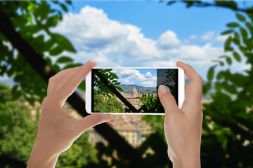 A man is making a photo of duomo Santa Maria del Fiore from one public park. Florence, Italy on a mobile phone