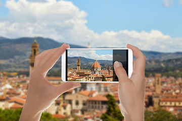 A man is making a photo of Panorama of Florence on a summer sunny day with the Duomo of Santa Maria del Fiore in the center on a mobile phone