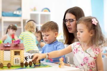 Teacher and group of kids buiding toy house with constructor in craft class