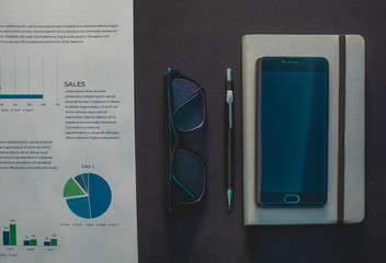 Glasses and phone lie on a black background next to a gray notepad and a sheet with a schedule