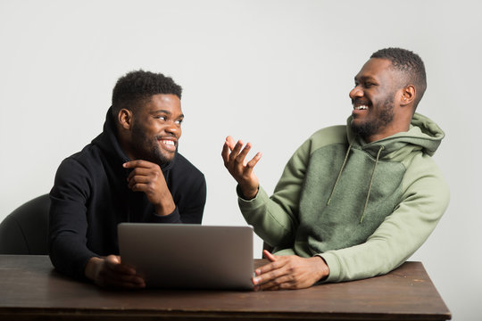 two sporty african men in tracksuits on a white background at a table with a laptop