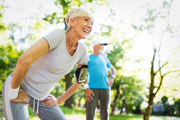 Happy mature couple stretching during running in the park Wall mural