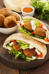 Falafel and fresh vegetables in pita bread with sauce.