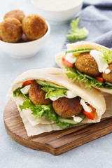 Pita breads with falafel, fresh vegetables and sauce.
