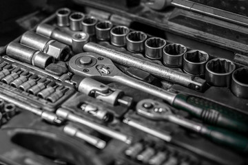 Flat Lay metal tools: wrenches, ratchet, a set of interchangeable heads of different sizes and other tools are in the tool box, a top view. Close-up Carpenter's Tool Kit