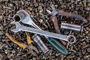 Flat Lay metal wrenches, ratchet, pliers, interchangeable tool heads of different sizes lie on the background of various metal cogs, screws and nails, top view. Close-up Carpenter's Tool Kit