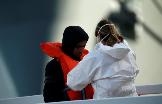 A police officer helps a migrant to remove a life jacket after disembarking from an Armed Forces of Malta (AFM) patrol boat which rescued 87 migrants, at the AFM's base at Haywharf in Valletta's Marsamxett Harbour