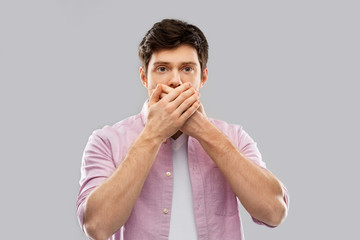 emotion, expression and people concept - shocked and speechless young man covering his mouth by hands over grey background
