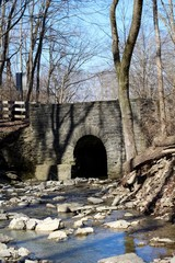 The old stone bridge over the flowing creek water.