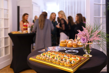 Delicious snacks on catering table during corporate event party - brunch choice of food with blurred group of people in background enjoying time together at business event party, Catering Food Concept