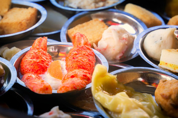 Traditional Asian dishes steamed in a bamboo basket - vegetables, mushrooms, shrimps, dough. Street food. Close-up