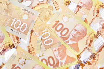 Canadian $100 dollar banknotes. The notes are dominantly brown in colour