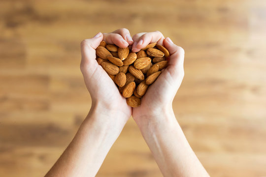 Young woman hands forming heart shape holding almonds nuts at home.