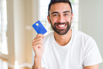 Handsome hispanic man holding credit card with a happy face standing and smiling with a confident smile showing teeth Wall mural