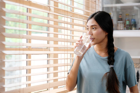 Youn beautiful asian woman drinking water while standing by window in kitchen background, peolpe and healthy lifestyles