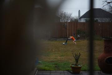 Asa Hoffmann pushes a toy lawnmower in his backyard in San Antonio, Texas