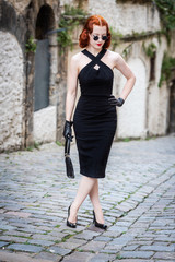 beautiful redhead woman in the street with black dress