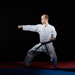 Adult athlete doing formal karate exercises on red and blue tatami
