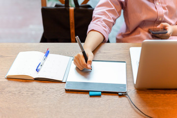Graphic designer using digital tablet with laptop on the desk.