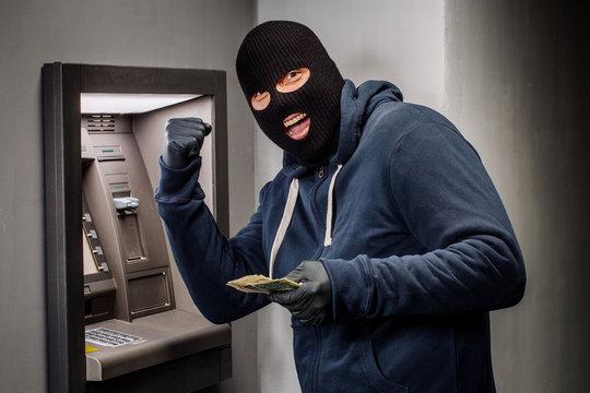 Thief. Hacker stealing money from ATM machine. Phishing, ATM skimming